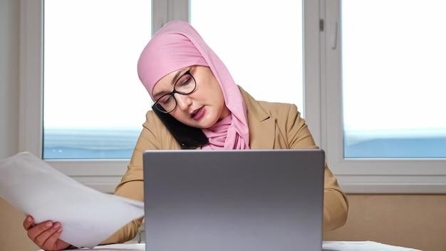 Kobieta w hidżabie analizuje dokumenty i pracuje na laptopie podczas rozmowy przez telefon