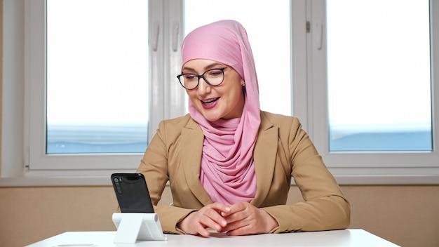 Kobieta w hidżabie i okularach siedzi przy stole i prowadzi rozmowę wideo przez telefon