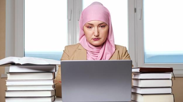 Kobieta w hidżabie, pisząc na laptopie wśród stosów książek.