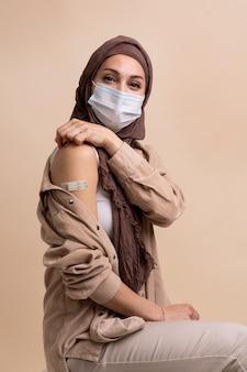 Kobieta w hidżabie pokazująca naklejkę na ramieniu po otrzymaniu szczepionki