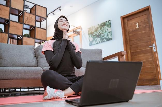 Kobieta w hidżabie siedzi ze skrzyżowanymi nogami z rękami pod brodą przed laptopem w domu