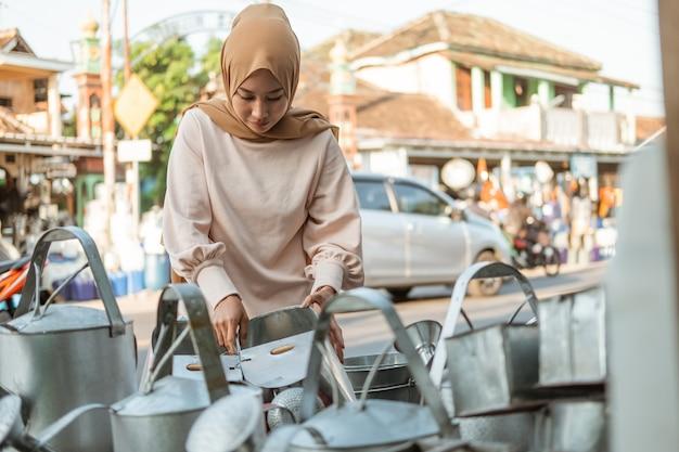Kobieta w hidżabie stoi przy wyborze konewki w sklepie ze sprzętem agd