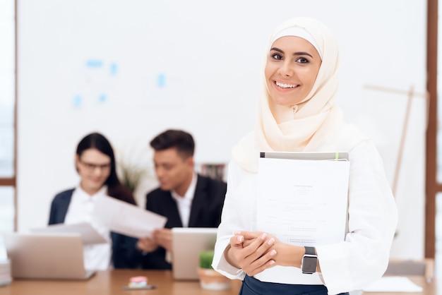 Kobieta w hidżabie stoi w call center.