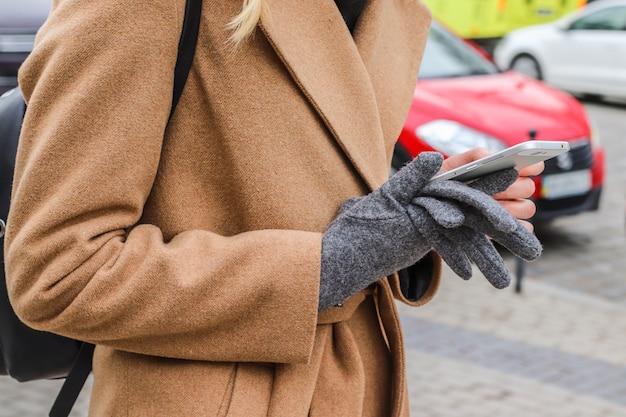 Kobieta w jaskrawym odzieżowym use telefon komórkowy przy plenerowym