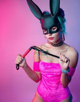 Kobieta w jasnoróżowym body i króliczej masce pozuje na jasnym tle