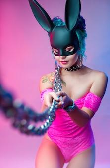 Kobieta w jasnoróżowym body i masce królika pozuje na jasnym tle z łańcuszkiem