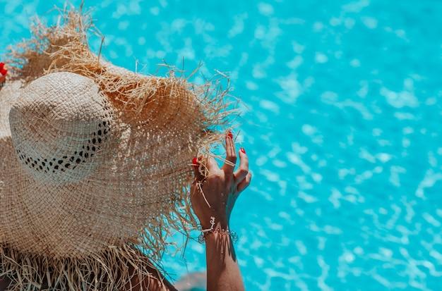 Kobieta w jasnym bikini i duży słomkowy kapelusz siedzący przy basenie. skopiuj miejsce. widok z tyłu.