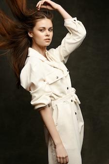 Kobieta w jasnym kombinezonie dotyka głowy ręką na ciemnym tle i rozpuszczonych rudych włosach