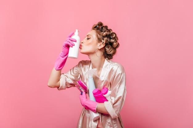 Kobieta w jedwabnej szacie i lokówkach całuje detergent do mycia naczyń