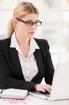 Kobieta w jej miejscu pracy. poważna dojrzała kobieta w stroju formalnym pracuje na laptopie siedząc w swoim miejscu pracy