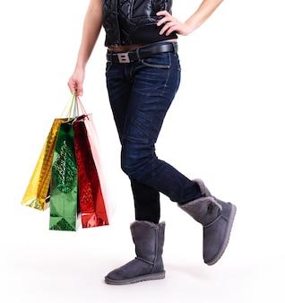 Kobieta w jesienne buty i niebieskie dżinsy z stojącymi torby na zakupy - na białym tle.