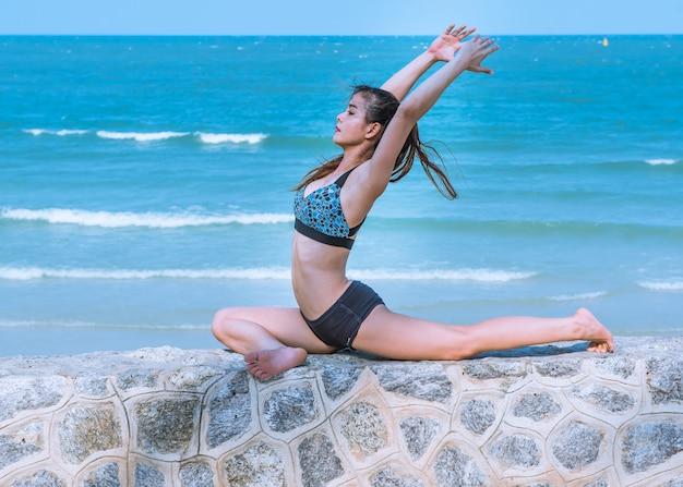 Kobieta w joga pozie przy plażą, joga rekolekcją i szkoleniem.