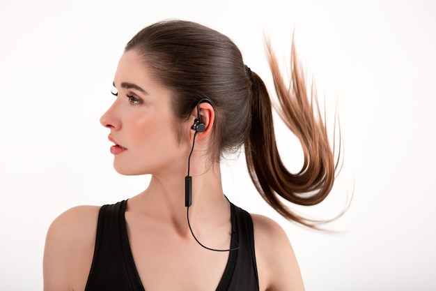 Kobieta w joggingu czarnym topu słuchająca muzyki na słuchawkach pozujących na białym tle