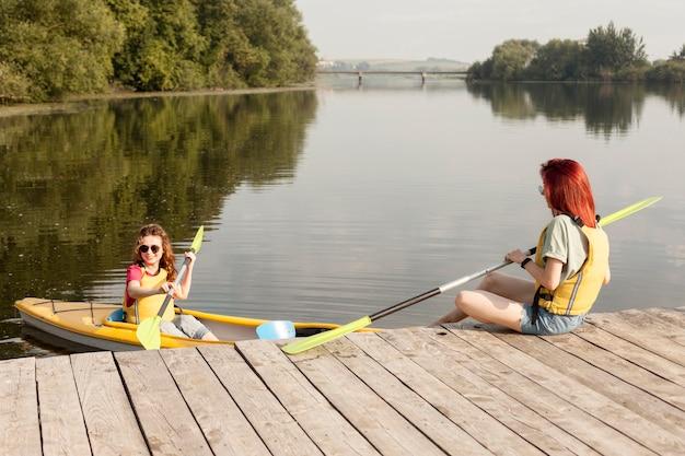 Kobieta w kajaku z przyjacielem trzymając wiosło na doku