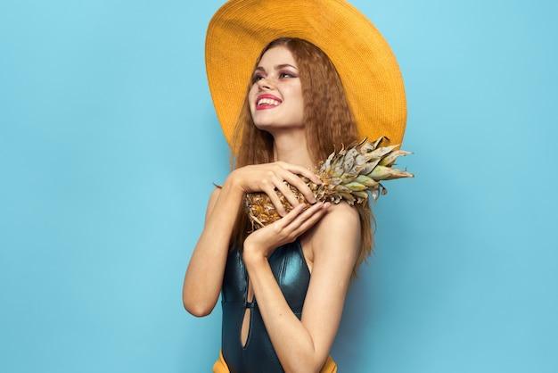 Kobieta w kapelusz plażowy ananas trzymając strój kąpielowy egzotyczne owoce niebieskie tło wakacje