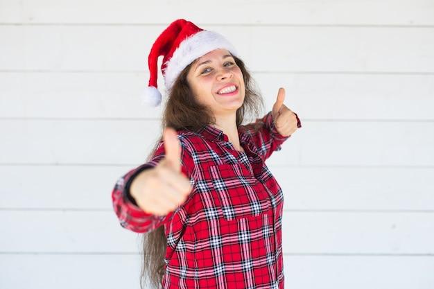Kobieta w kapeluszu boże narodzenie pokazując kciuki do góry na białej ścianie