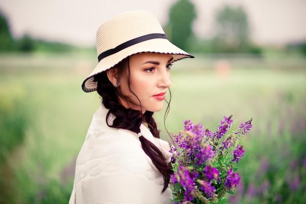 Kobieta w kapeluszu gospodarstwa bzu kwiaty na łące.