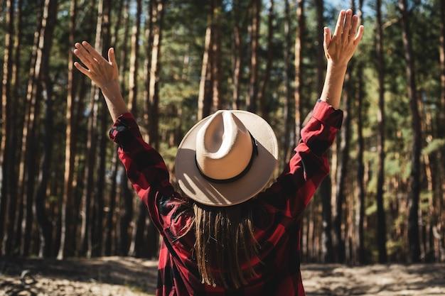 Kobieta w kapeluszu i czerwonej koszuli w kratę w lesie.