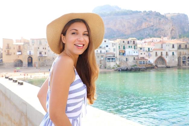 Kobieta w kapeluszu i letniej sukience patrząc na kamery z miejscowością cefalu w tle, wyspa sycylia, włochy