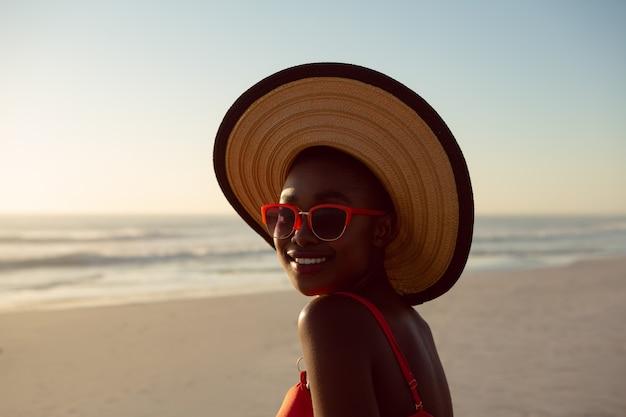 Kobieta w kapeluszu i okularach przeciwsłonecznych relaksuje na plaży