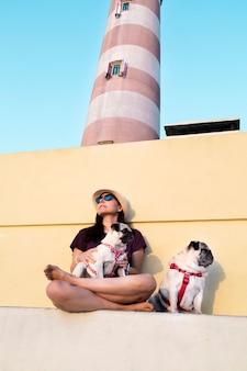 Kobieta w kapeluszu i okularach przeciwsłonecznych z psami o zachodzie słońca obok latarni morskiej aveiro w portugalii