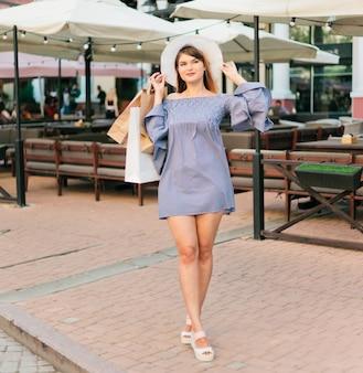 Kobieta w kapeluszu i sukni trzyma w rękach torby na zakupy i uśmiecha się w letnim mieście