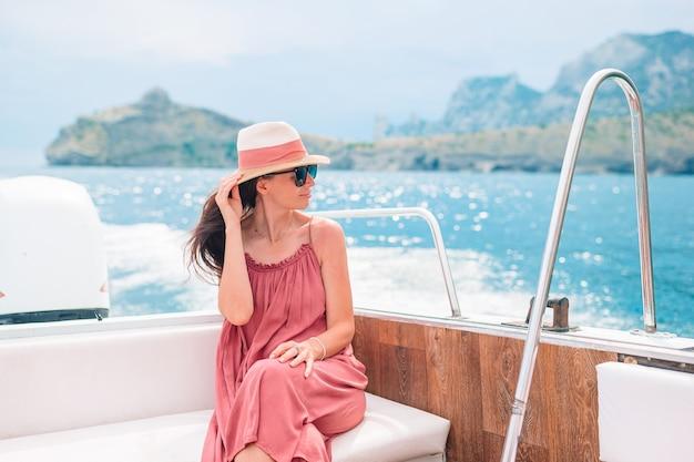 Kobieta w kapeluszu i sukni żeglowania na łodzi w czystym morzu