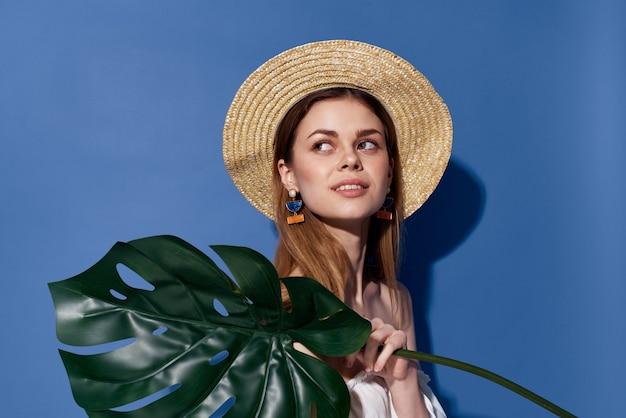Kobieta w kapeluszu liści palmowych podróży lato egzotyczne niebieskie tło. wysokiej jakości zdjęcie