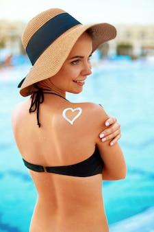 Kobieta w kapeluszu na brzegu basenu nakładając krem do opalania w kształcie serca na opalone ramię.