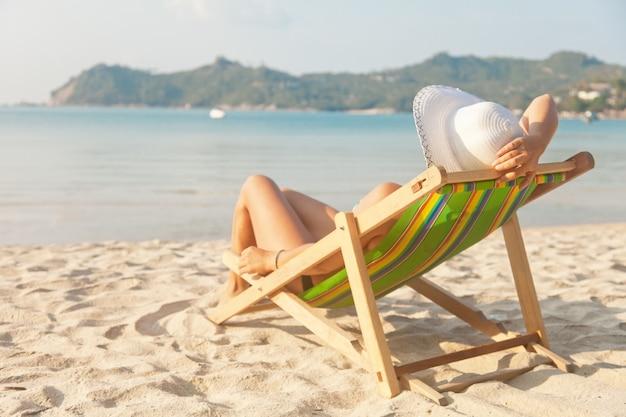 Kobieta w kapeluszu na plaży, siedząc na leżaku i obserwując morze