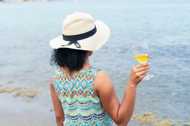 Kobieta w kapeluszu na plecach trzymająca kieliszek wina