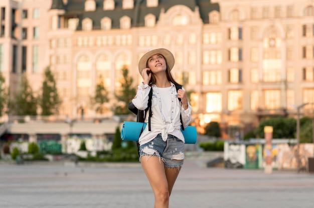 Kobieta w kapeluszu niosąca plecak podczas podróży i patrząc w górę