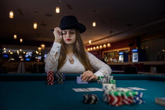 Kobieta w kapeluszu oferująca żetony z kasyna na dłoni