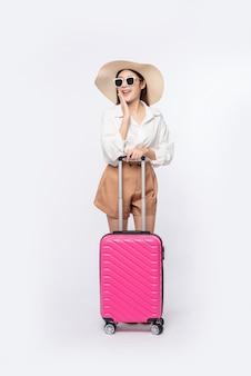 Kobieta w kapeluszu, okularach i uchwytach walizek do podróży