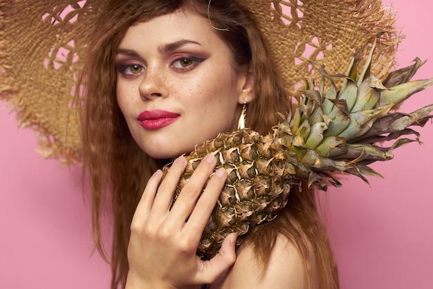 Kobieta w kapeluszu plażowym ananasa egzotyczny strój kąpielowy różowy