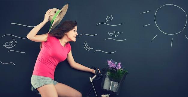 Kobieta w kapeluszu podczas jazdy na rowerze