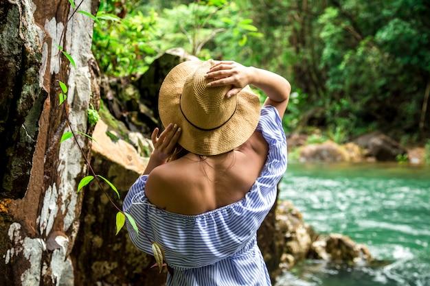 Kobieta w kapeluszu przy rzeką