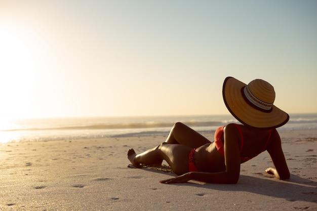 Kobieta w kapeluszu relaksuje na plaży