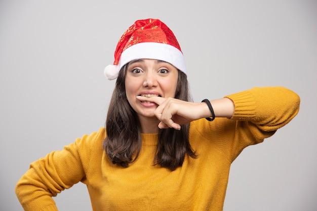 Kobieta w kapeluszu santa gryzie palec na szarej ścianie.
