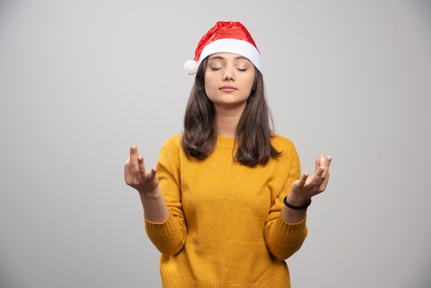 Kobieta w kapeluszu santa robi medytację na szarej ścianie.