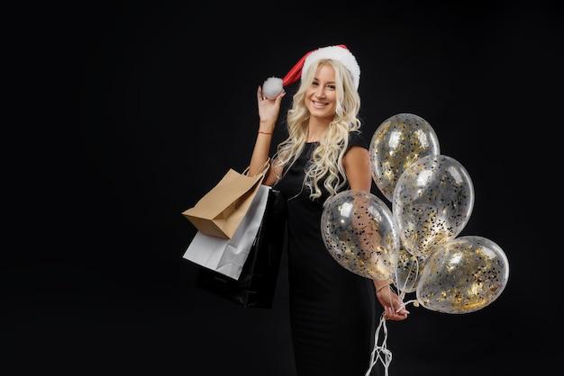 Kobieta w kapeluszu santa. wigilia na czarnej ścianie, torbach na zakupy i złotych balonach