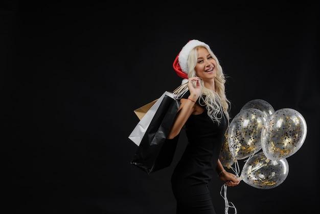 Kobieta w kapeluszu santa. wigilia na czarnej ścianie, torby na zakupy i złote balony