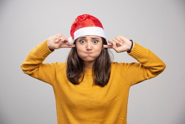 Kobieta w kapeluszu santa zakrywająca uszy i wstrzymująca oddech.
