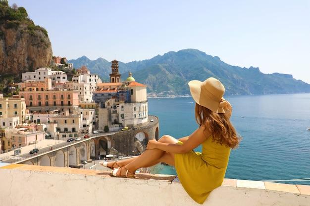 Kobieta w kapeluszu siedzi na ścianie patrząc na wioskę atrani na wybrzeżu amalfi we włoszech