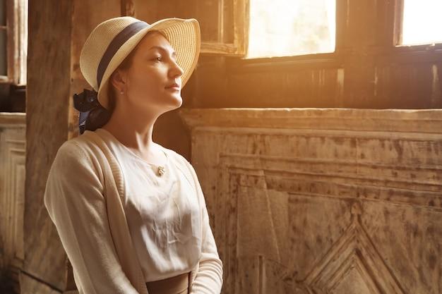 Kobieta w kapeluszu stoi przy oknie w muzeum hagia sophia. światło słoneczne.