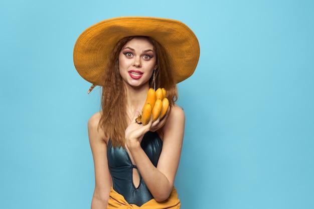 Kobieta w kapeluszu strój kąpielowy egzotyczne owoce letnie zabawy niebieskie tło