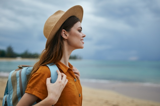 Kobieta w kapeluszu sundress z plecakiem na bac