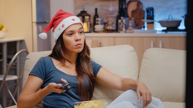 Kobieta w kapeluszu świętego mikołaja ogląda telewizję w wigilię bożego narodzenia