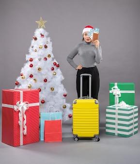 Kobieta w kapeluszu świętego mikołaja z bagażem obok choinki