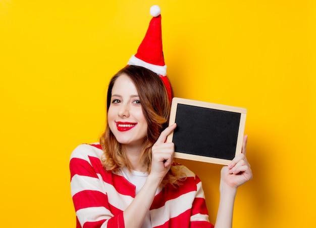 Kobieta w kapeluszu święty mikołaj z tablicą